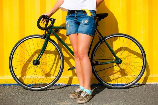 Chica y una bicicleta deportiva sobre un fondo amarillo