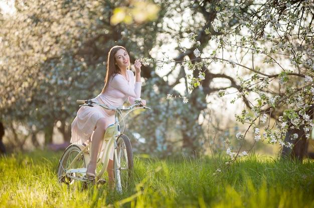 Chica con una bicicleta en los rayos de sol en el jardín de primavera