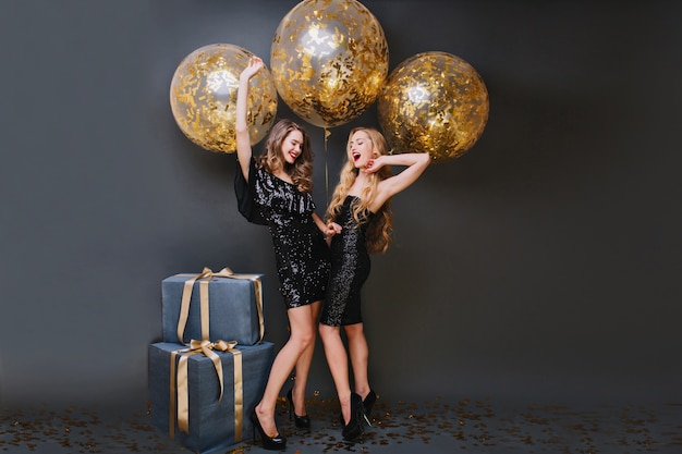 Chica bien formada con el pelo largo y rizado jugando con su hermana durante la sesión de fotos de cumpleaños. encantadoras damas con vestidos de moda esperando la fiesta, de pie junto a los regalos.
