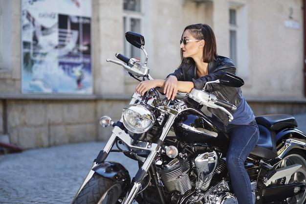 Chica biker en una chaqueta de cuero en moto
