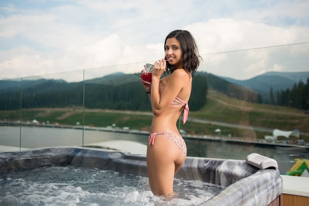 Chica en bikini en el jacuzzi al aire libre