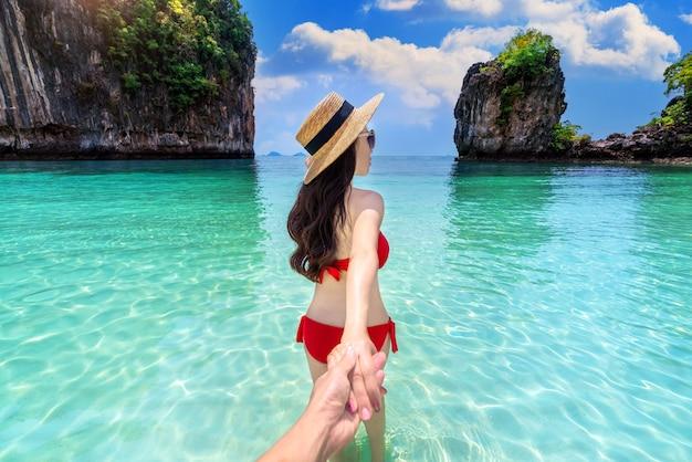 Chica bikini sujetando la mano del hombre y llevándolo a la isla de koh hong en krabi, tailandia