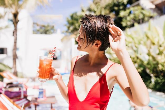 Chica blanca delgada posando con una copa de cóctel en el resort.
