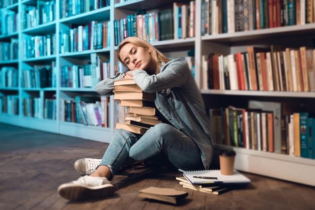 Chica blanca está durmiendo con libros en su regazo.