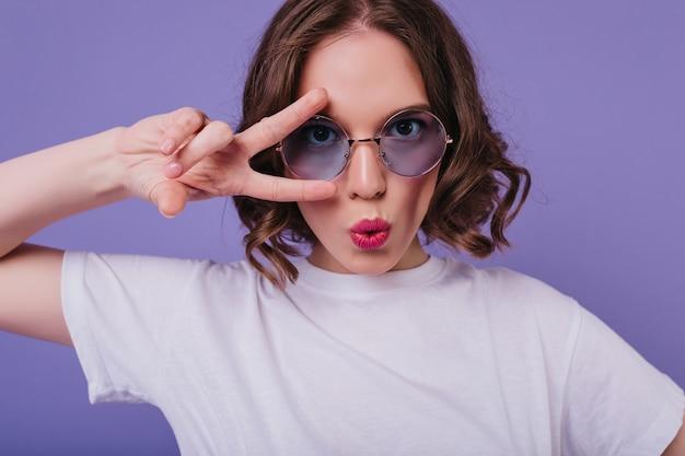 Chica blanca guapa lleva camiseta posando con el signo de la paz en estudio. modelo de mujer morena alegre en gafas de sol divirtiéndose en la pared púrpura.