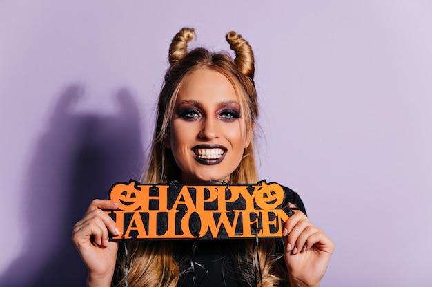 Chica blanca refinada posando con decoración de halloween. impresionante mujer elegante preparándose para la fiesta de terror.