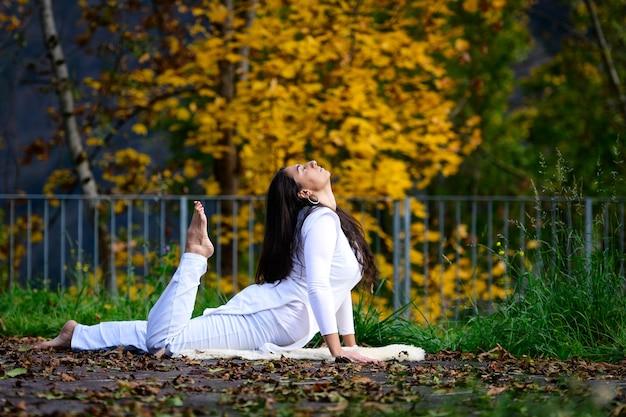 Chica de blanco en posición de yoga en el parque