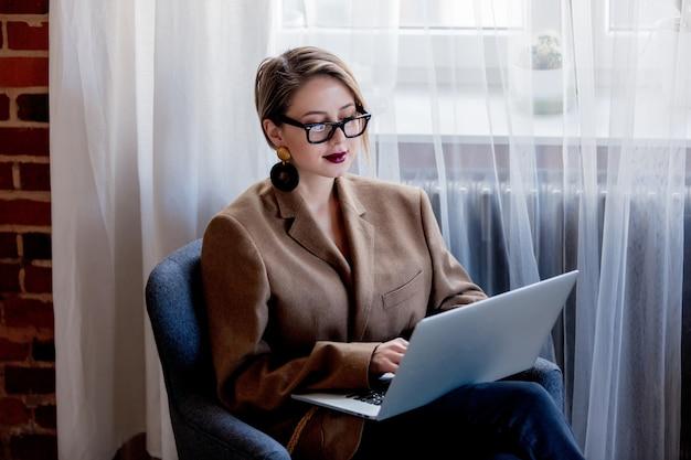 Chica en blazer y gafas trabajando con computadora portátil