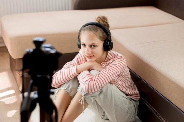 Chica blogger con cámara y auriculares.