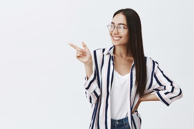 Chica con blusa a rayas de moda y gafas sosteniendo la mano en la cadera, mirando con admiración e interés, apuntando hacia la izquierda con el dedo índice mientras está de pie sobre una pared gris, asistiendo a una exposición curiosa