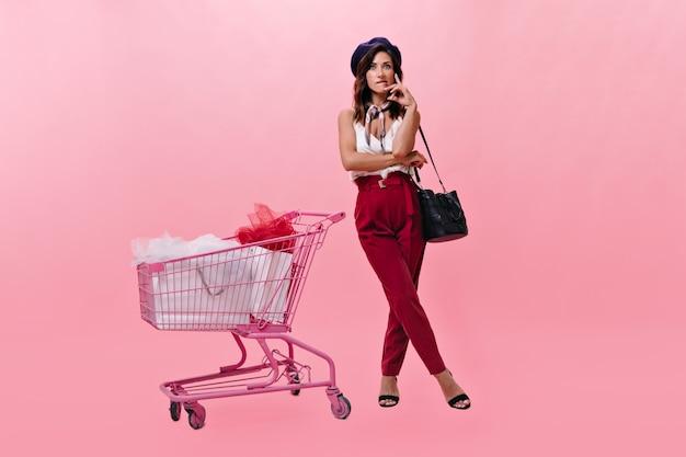 Chica con boina y pantalones brillantes mira a la cámara pensativamente y posa junto al carrito del supermercado. foto de mujer con elegante traje brillante sobre fondo rosa.