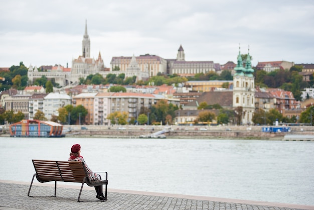 Chica de boina roja se sienta en un banco