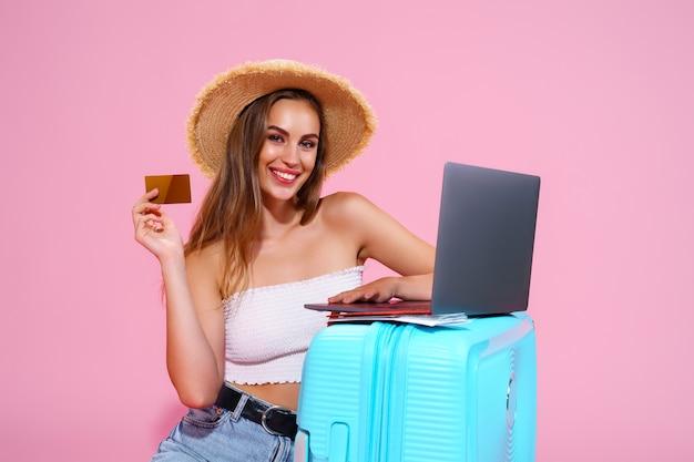 Chica con boletos para computadora portátil, tarjeta de crédito y pasaporte va a viajar sentada cerca de la maleta en breve ...