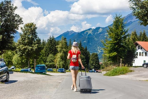 Chica con bolsa en el estacionamiento en el aeropuerto.