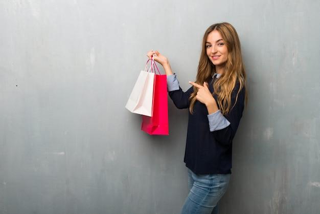 Chica con bolsas de compras apuntando con el dedo hacia un lado en posición lateral