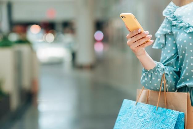 Chica con bolsas de compras con fondo borroso