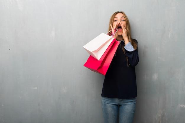 Chica con bolsas de compras gritando y anunciando algo.