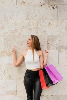 Chica con bolsas de compras de pie junto a la pared