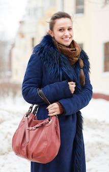 Chica con bolso en la calle de invierno