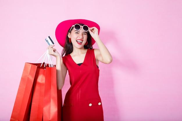 Chica bonita asiática sosteniendo bolsas de compras mientras espera tarjetas de crédito y gafas de sol