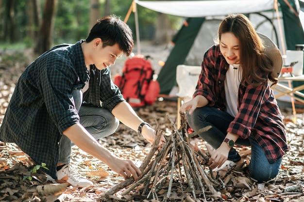 Chica bonita campista preparando leña con su novio para iniciar una fogata. pareja de jóvenes turistas ayudando a recoger ramas y juntarlas en la parte delantera de la tienda de campaña