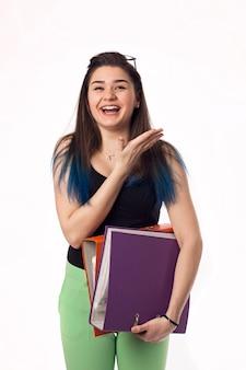 Chica bonita morena estudiante en vasos con carpetas de colores