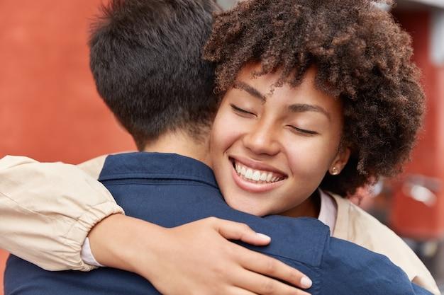 La chica bonita de piel oscura complacida tiene una sonrisa con dientes, mantiene los ojos cerrados, abraza a su viejo amigo, tiene una buena relación