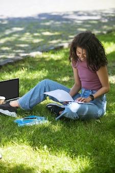Una chica bonita de piel oscura estudiando en el parque.