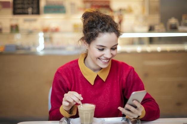 Chica bonita revisando su teléfono inteligente en un café