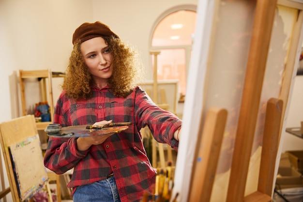 Chica bonita rizada vestida con boina y camisa dibuja una imagen