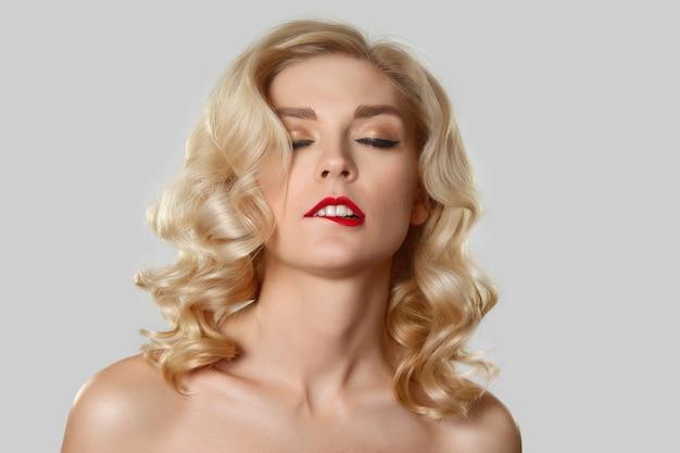 Chica bonita rubia con cabello ondulado, maquillaje de ojo de gato mordiendo sus labios rojos