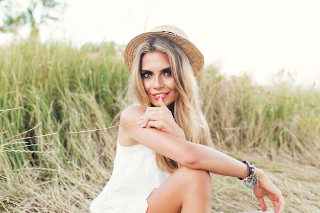 Chica bonita rubia con pelo largo está posando para la cámara en el fondo del campo. lleva sombrero, vestido blanco y sonríe a la cámara.