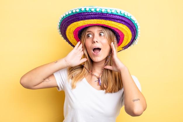Chica bonita rubia que se siente feliz, emocionada y sorprendida. concepto de sombrero mexicano