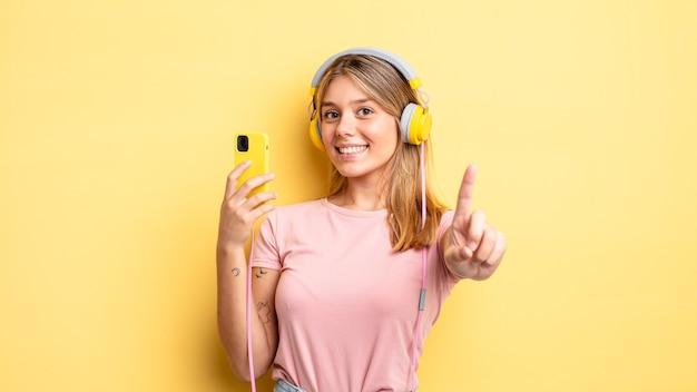 Chica bonita rubia sonriendo con orgullo y confianza haciendo el número uno. escuchando musica concepto