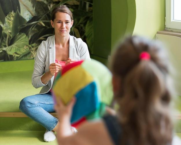 Chica borrosa sosteniendo bola colorida
