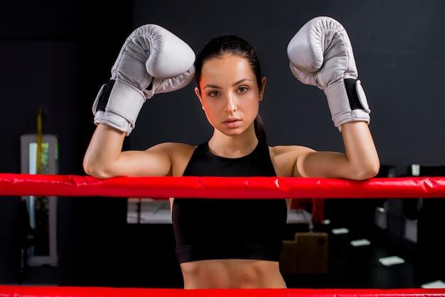 Chica boxeadora posando en el gimnasio