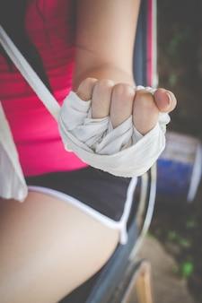 Chica boxer envolviendo las manos con un paño blanco
