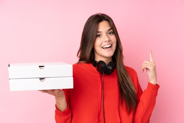Chica brasileña adolescente sosteniendo cajas de pizza sobre pared rosa aislado apuntando hacia arriba una gran idea