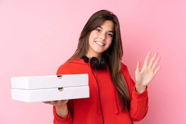 Chica brasileña adolescente sosteniendo cajas de pizza sobre pared rosa aislado saludando con la mano con expresión feliz