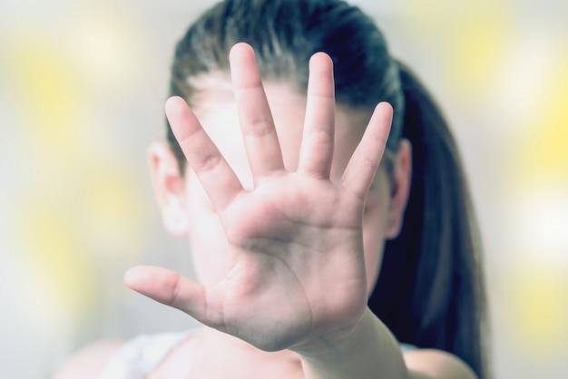 Chica con el brazo extendido y los dedos. el concepto de abuso infantil.