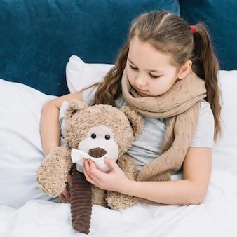 Chica con bufanda alrededor de su cuello cubriendo la boca de un oso de peluche con un pañuelo de papel
