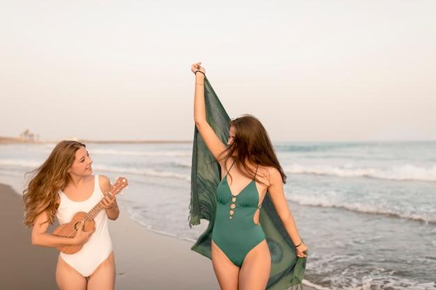 Chica con bufanda bailando con su amiga jugando ukelele en la playa