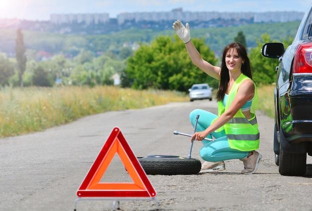 Chica busca ayuda con el reemplazo de la rueda de repuesto