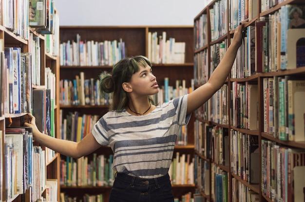 Chica buscando un libro en una estantería