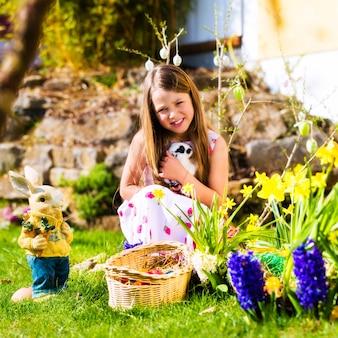 Chica en búsqueda de huevos de pascua con conejito de pascua vivo