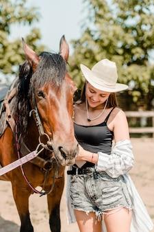Chica con un caballo marrón en la granja