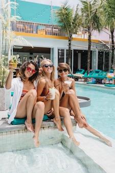Chica de cabello castaño relajándose en la piscina con mejores amigos. señoras bronceadas guapas bebiendo cócteles en un complejo exótico.