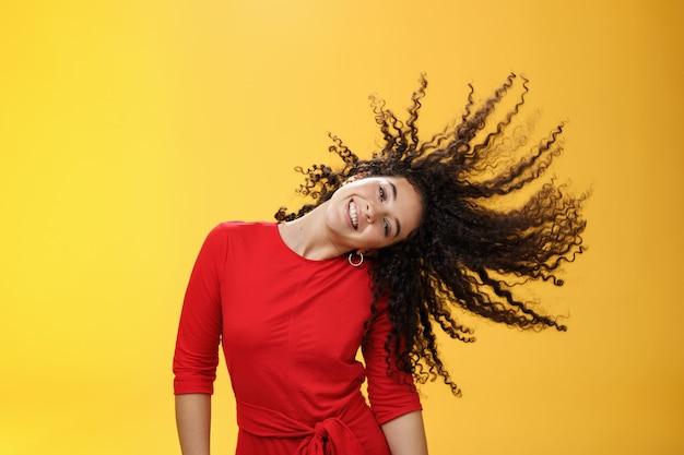 Chica con cabello ondulado despreocupado y salvaje y haciendo sol con rizos volando en el aire sonriendo ampliamente inclinando la cabeza y divirtiéndose, bailando encantada y divertida sintiéndose juguetona contra el fondo amarillo.