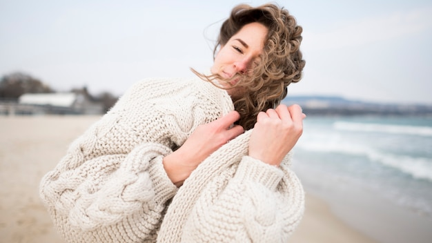 Chica con cabello ondulado y océano