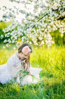 Chica con una cabra sentada en la hierba en un exuberante huerto de manzanas